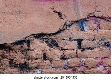Old brick wall with peeling stucco. Weathered rough wall surface with brickwork. The wall is painted in different colors. Vintage background. Urban texture.