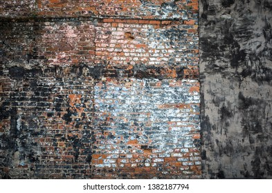 Old brick wall from the side of a demolished building revealing old paint and plaster. Great for a grungy background.