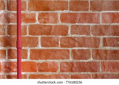 Old brick wall, texture of red stone blocks with pipe. Close up. Weathered red grungy brick wall background. Architecture detail. Copy space.