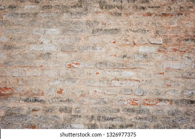Old brick wall texture with scratches and crack. Ancient stone wall. Yellow grunge texture of old brick