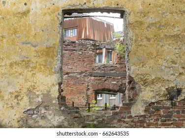 Old brick wall texture, with a window in it and a view on other buildings.
