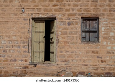 An old brick wall with a very very weathered wooded door and window.