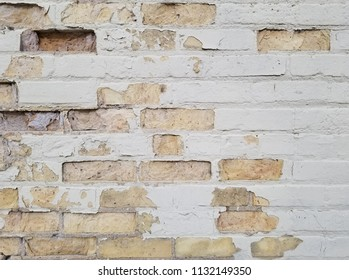 Old brick wall with weathered & chipped white paint. Exposed brick & mortar. Horizontal detail.