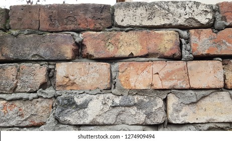 Old brickwork wall with rough cement joints. Grunge grey brown brick wall background with cracked brick surface closeup. Weathered brick wall texture. Brick pattern background. Masonry backdrop