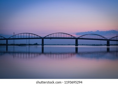 Old bridge of arches with reflection on the river