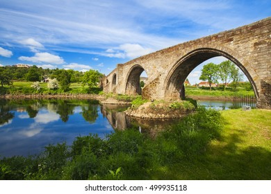 Old bridge with arches, turrets and buttresses crosses the Forth in Stirling, Scotland, scene of the historic Battle of Stirling Bridge where Scots led by William Wallace defeated the English in 1297.