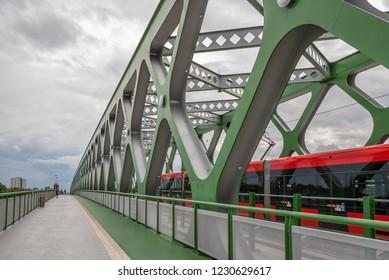 The Old Bridge over the Danube River in Bratislava, Slovakia.A green truss steel bridge , a red tram passing along it and a pedestrian promenade.
