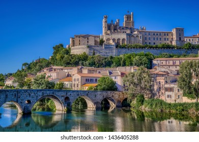 The Old Bridge (Pont Vieux) and Saint Nazaire Cathedral, landmarks in the city of Beziers, Herault Department, France, seen from the River Orb on a summer's evening
