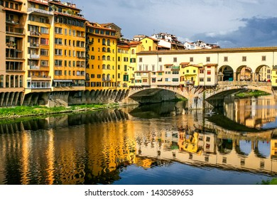Old bridge Ponte Vecchio with colourful buildings houses and its reflection in the river Arno in Florance, Tuscany, Italy. April 2012