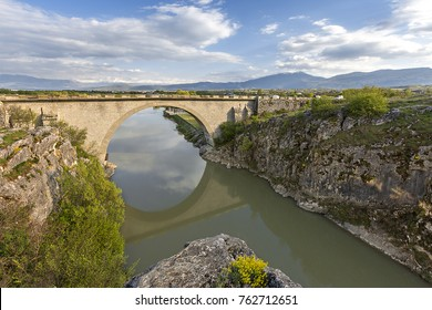 Old bridge with its reflections in water, near Prizren, Kosovo.