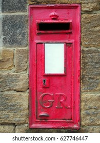 Old British Red post box set in a stone wall