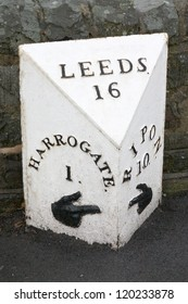An old British road sign showing distances to Harrogate, Ripon and Leeds