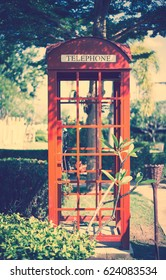 Old British Telephone box pay phone in forest vintage tone