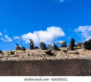 Old, broken bottles in set in concrete as a security barrier on a wall.