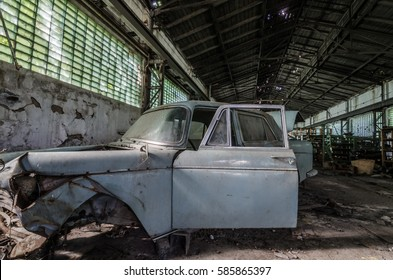 old broken car in large storehouse