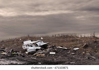 Old broken car thrown at a garbage dump, amid unnecessary trash