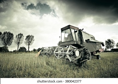 Old broken combine harvester abandoned in the field during work. Retro style, deep contrast.