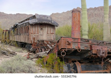 Old broken derelict wooden railroad car in an Arizona desert landscape with saguaro cacti