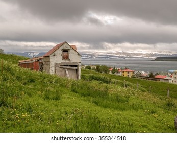 Old broken down house on a green hillside looking over the water in Isafjordur Iceland.