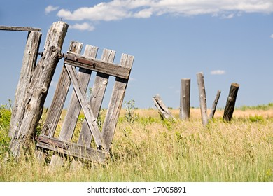 old broken fence door hangs crooked on a post