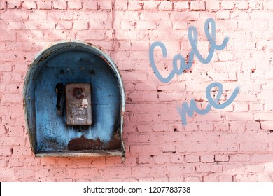 Old broken phone of the Soviet period on the pink brick wall of the house and the inscription: call me. Blue phone booth