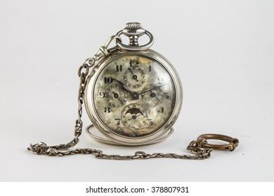 old broken pocket watch on a white background