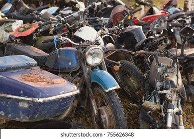 The old broken rusty bicycles, motorcycles, toy cars, engines, tires and wheels with spokes in the open air on the ground