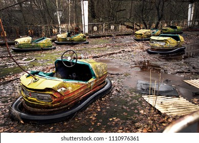 Old broken rusty metal radioactive yellow cars, children's electric cars, abandoned among vegetation, the park of culture and recreation in the city of Pripyat, the Chernobyl disaster, Ukraine.