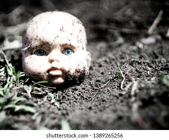 Old broken scary doll head on a ground in abandoned village.