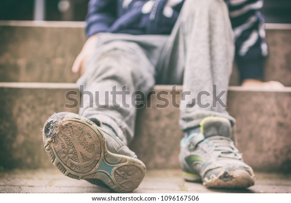 Old broken shoes of a little boy as a symbol for child poverty