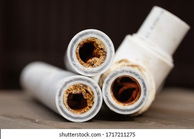 Old broken sludge polypropylene plumbing pipes with red rust and limescale. Corrosion, sludge and hard water concept. Rust broken water pipes