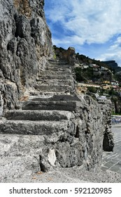 Old broken steps leading up from the harbour area at Positano, Italy