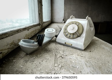 Old broken telephone on a windowsill of an abandoned office