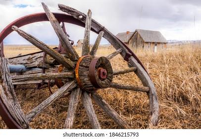 Old broken wagon wheel in farm field. Fagon wheel. Abandoned wagon wheel. Old wagon wheel is broken