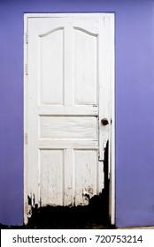 Old broken white door and purple color wall