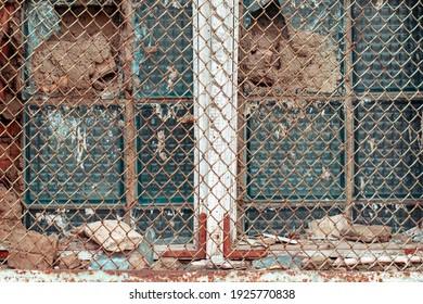 Old broken window with a rusty metal grate. An old broken window behind an iron mesh