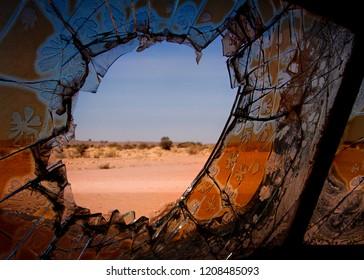 Old broken windsheild of a deserted car, looking out on to a desert landscape