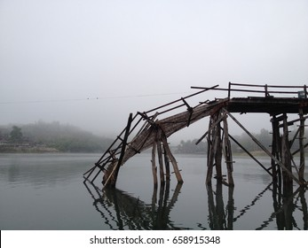 The old and broken wooden bridge over the river. Travel, tourism, holidays, and construction concept