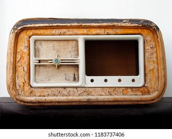 An old broken wooden vintage radio receiver with a cracked brown case and missing parts