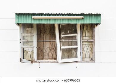 Old broken wooden windows on white concrete wall.