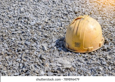Old broken yellow durable plastic safety helmet hat for engineer or worker placed on gravel floor in a construction area for security and protection from the accident concept