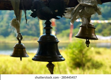 Old bronze bells in indian temple in front of shining green lawn