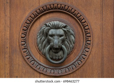 Old bronze lion head door knocker in a wooden circular frame