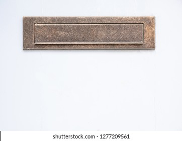 Old bronze mailbox. Brass vintage mail letter box on white color wall background. Closeup view with details