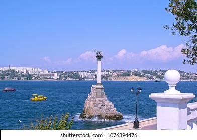 Old bronze monument to Russian ships in Sevastopol (Russia) scuttled to blockade harbor (in Crimean War). Embankment. Panoramic view of city on sea coast.