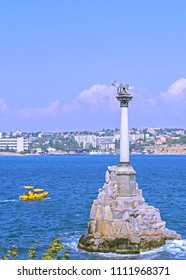 Old bronze monument to Russian ships in Sevastopol scuttled to blockade harbor (in Crimean War). View of sea, city & small holiday cruiser.