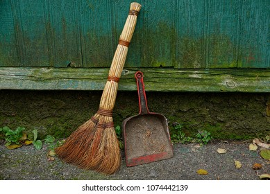 Old broom and dirty scoop near the wooden green wall