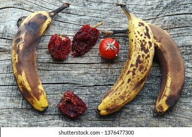 Old brown bananas and dried peppers and tomatoes. Old fruit and vegetables