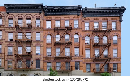 old brown brick New York apartment building with external fire escape ladders
