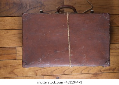 Old brown cardboard suitcase on background wooden floor